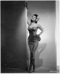 Unidentified woman wearing evening dress posed with right arm extending up wall